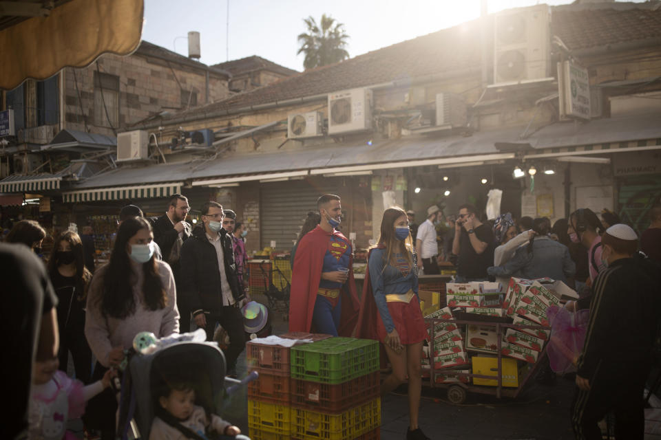 A couple wears Superman and Supergirl costumes for the Jewish holiday of Purim, as they stroll through the Mahane Yehuda Market in Jerusalem, Friday, Feb. 26, 2021. Israel has instituted a nightly curfew during the holiday to curb the spread of the coronavirus. (AP Photo/Maya Alleruzzo)