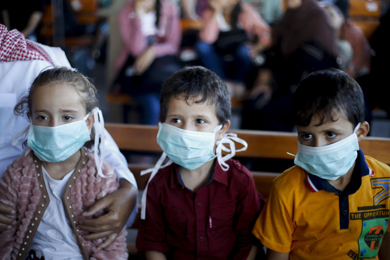 GAZA, PALESTINE - 2020/08/11: Palestinian children wearing protective masks, are seen seated as they wait to leave through the Rafah border crossing with Egypt. Egypt reopens the Rafah land crossing after months of closure due to the Coronavirus pandemic in the southern Gaza Strip. (Photo by Yousef Masoud/SOPA Images/LightRocket via Getty Images)