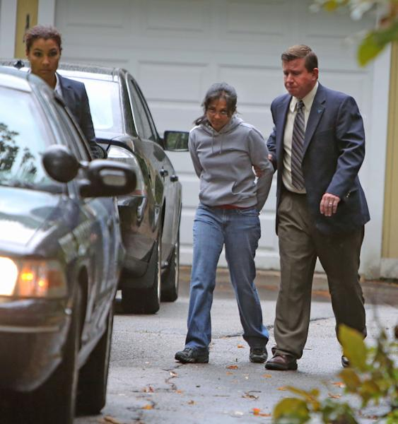 Annie Dookhan, center, is escorted to a cruiser outside her home in Franklin, Mass. Friday, Sept. 28, 2012. Dookhan is accused of faking drug results, forging signatures and mixing samples a state police lab. State police say Dookhan tested more than 60,000 drug samples involving 34,000 defendants during her nine years at the lab. Defense lawyers and prosecutors are scrambling to figure out how to deal with the fallout. (AP Photo/Bizuayehu Tesfaye)