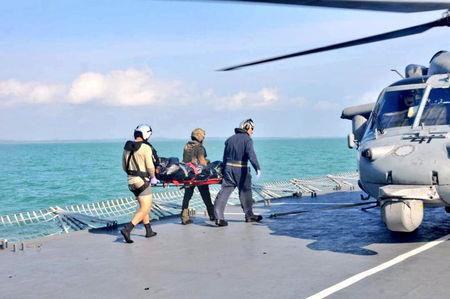 Royal Malaysian Navy personnel carry a body onto a U.S. Navy helicopter from USS America during a search and rescue operation for survivors of the USS John S. McCain ship collision in Malaysian waters August 23, 2017. Royal Malaysian Navy Handout via REUTERS