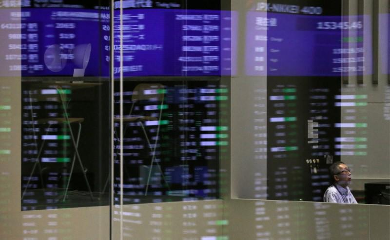 Market prices are reflected in a glass window at the Tokyo Stock Exchange (TSE) in Tokyo, Japan, February 6, 2018. REUTERS/Toru Hanai