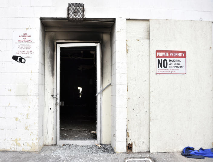 Soot darkens the backdoor of a three-story apartment complex Saturday, Dec. 21, 2019 in Las Vegas. The fire was in first-floor unit of the Alpine Motel Apartments and its cause was under investigation, the department said. Authorities say multiple fatalities were reported and many more were injured. (AP Photo/David Becker)