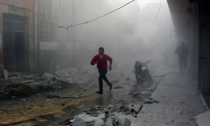 Residents flee after an airstrike on Aleppo in 2014.