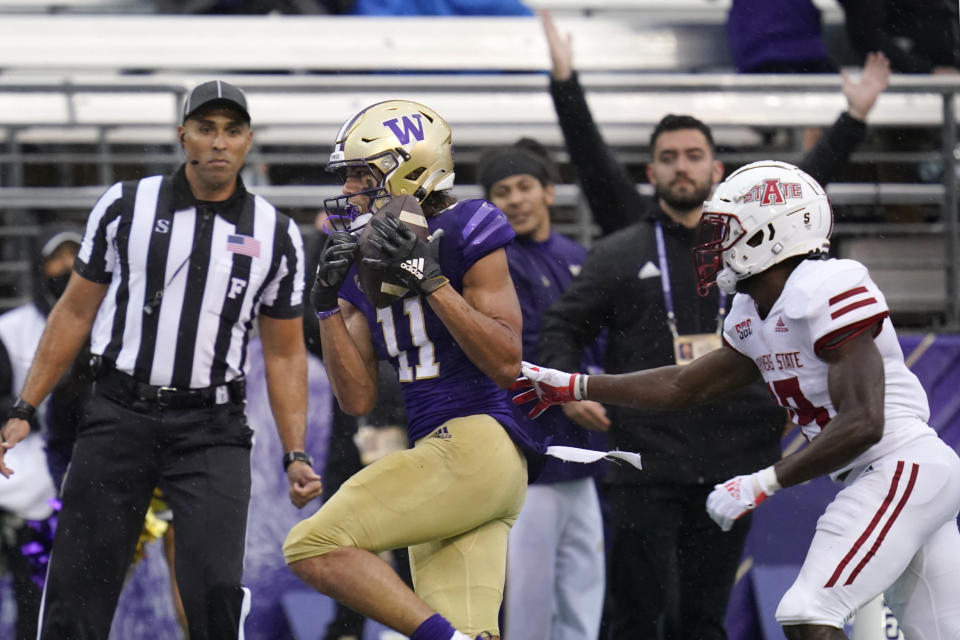 Washington's Jalen McMillan (11) scores on a 33-yard pass reception as Arkansas State's Denzel Blackwell defends in the first half of an NCAA college football game, Saturday, Sept. 18, 2021, in Seattle. (AP Photo/Elaine Thompson)