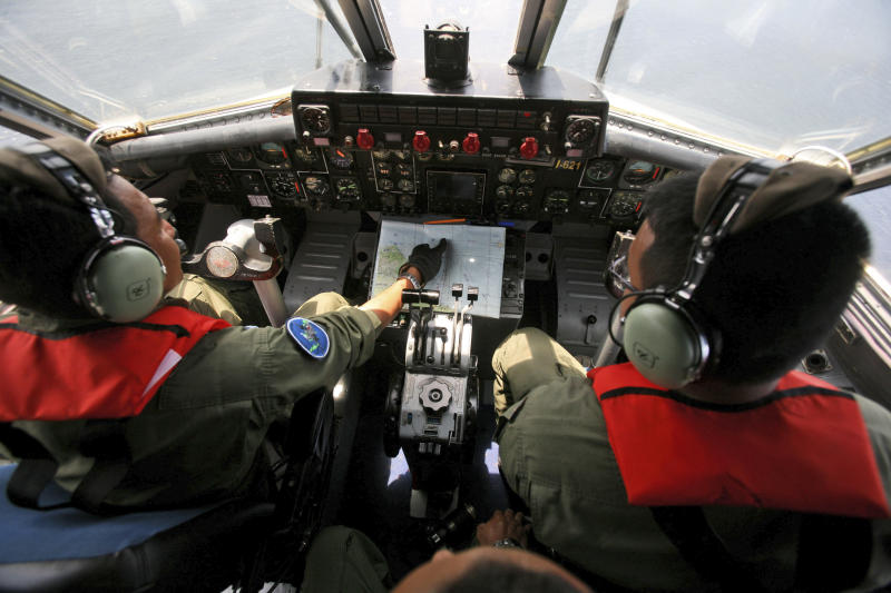 """Indonesian Navy pilots Maj. Bambang Edi Saputro, left, and 2nd Lt. Tri Laksono check their map during a search operation for the missing Malaysian Airlines Boeing 777 over the waters bordering Indonesia, Malaysia and Thailand near the Malacca straits on Monday, March 10, 2014. Dozens of ships and aircraft have failed to find any piece of the missing Boeing 777 jet that vanished more than two days ago above waters south of Vietnam as investigators pursued """"every angle"""" to explain its disappearance, including hijacking, Malaysia's civil aviation chief said Monday. (AP Photo/Binsar Bakkara)"""