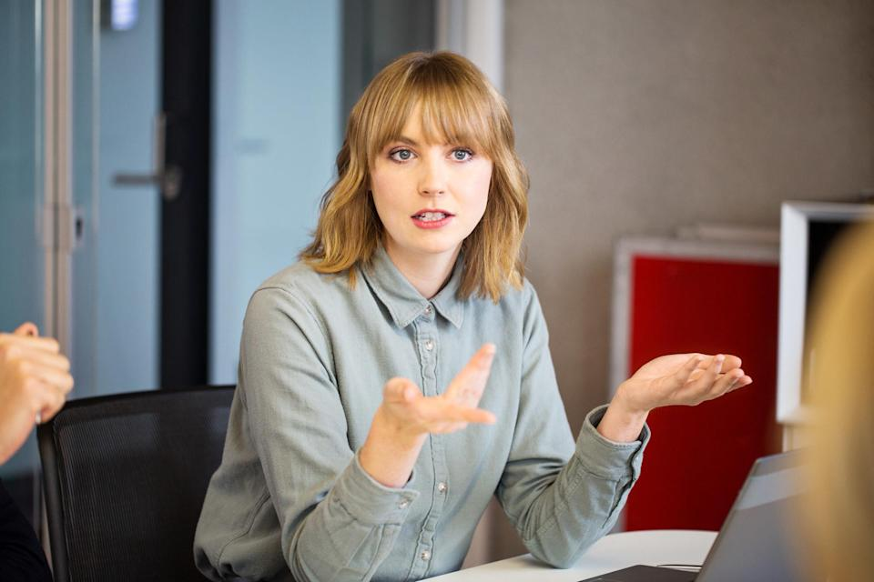 A woman in a conference room asking a question