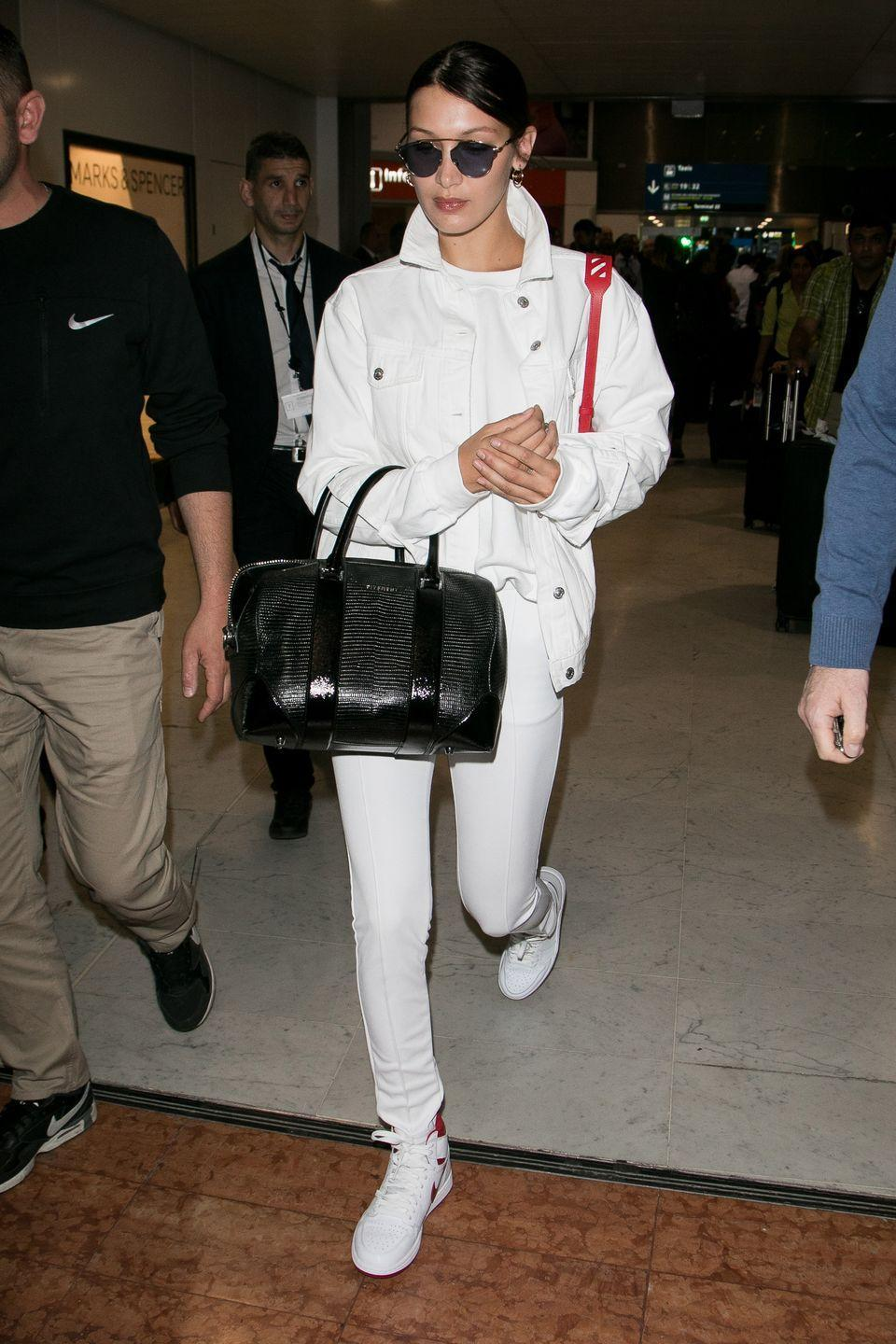 <p>In a white jacket, top and jeans, Nike sneakers, black leather satchel and Dior sunglasses at the Paris airport.</p>