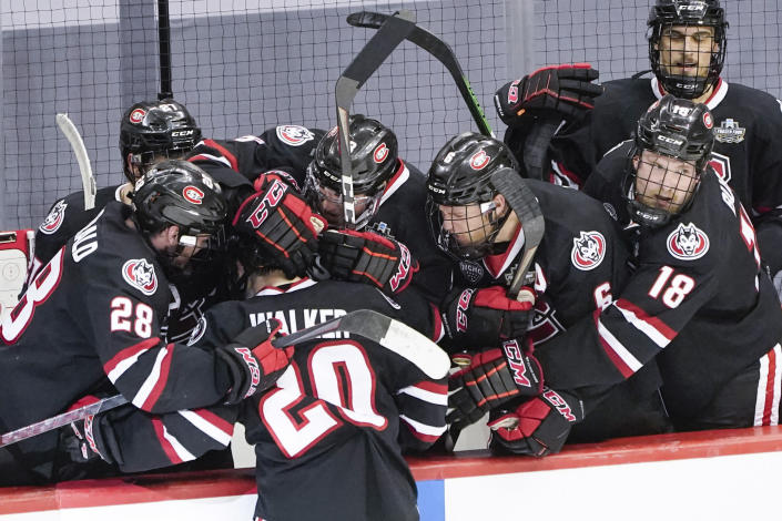 St. Cloud State's Nolan Walker (20) is greeted by teammates after scoring against Minnesota State to break a tie with less than a minute left in an NCAA men's Frozen Four hockey semifinal in Pittsburgh, Thursday, April 8, 2021. St. Cloud State won 5-4 to advance to the championship game Saturday. (AP Photo/Keith Srakocic)