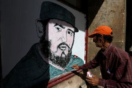 A local artist paints a portrait of Fidel Castro in front of a shop in downtown Havana, following the announcement of the death of the Cuban revolutionary leader, in Cuba