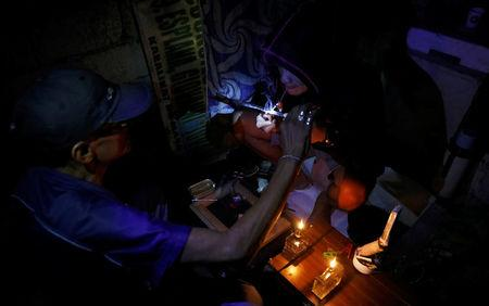 "A drug user inhales ""Shabu"", or methamphetamine, at a drug den in Manila, Philippines February 13, 2017.     REUTERS/Erik De Castro"