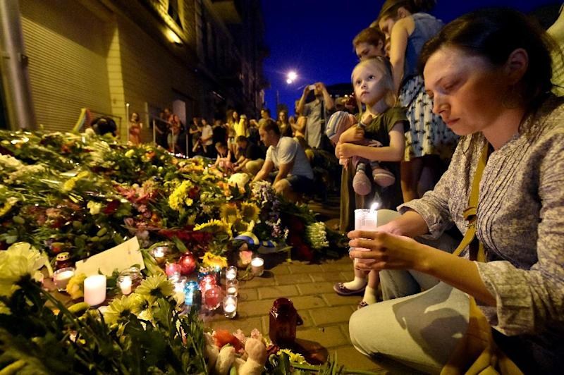 A woman lights a candle in front of the Embassy of the Netherlands in Kiev on July 17, 2014, to commemorate passengers of Malaysian Airlines flight MH17