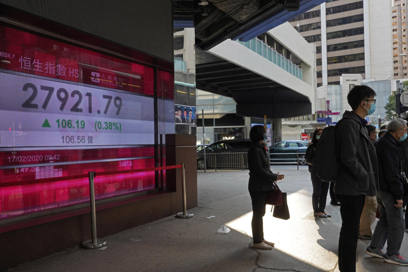 People stand in front of a bank electronic board showing the Hong Kong share index at Hong Kong Stock Exchange Monday, Feb. 17, 2020. Markets are mixed in Asia, with Japan's benchmark slipping 0.8% after the government reported the economy contracted in the last quarter. (AP Photo/Vincent Yu)