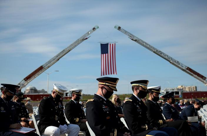 U.S. service members sit in chairs while a U.S. flag hangs from two cranes behind them