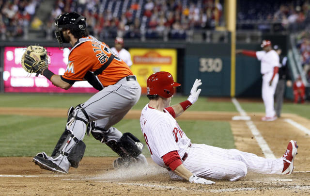 Philadelphia Phillies' Chase Utley, right, beats the throw to Miami Marlin's Jarrod Saltalamacchia, left, to score from second base on a single by Marlon Byrd during the fifth inning of a baseball game on Friday, April 11, 2014, in Philadelphia. (AP Photo/Tom Mihalek)