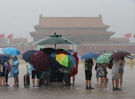Tourists hold umbrellas as they visit Tiananmen Square during a rainstorm in Beijing