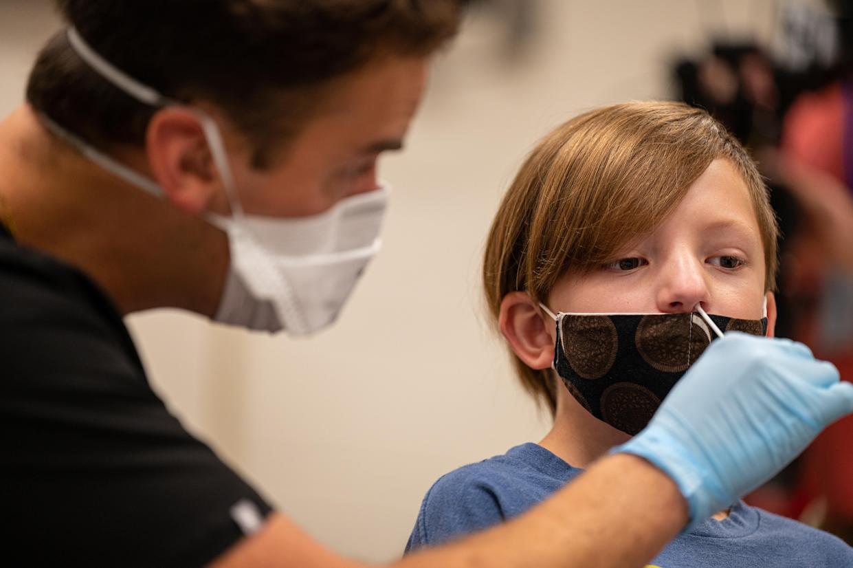 A health care worker wearing a face mask and rubber gloves, inserts a swab into the nose of student.