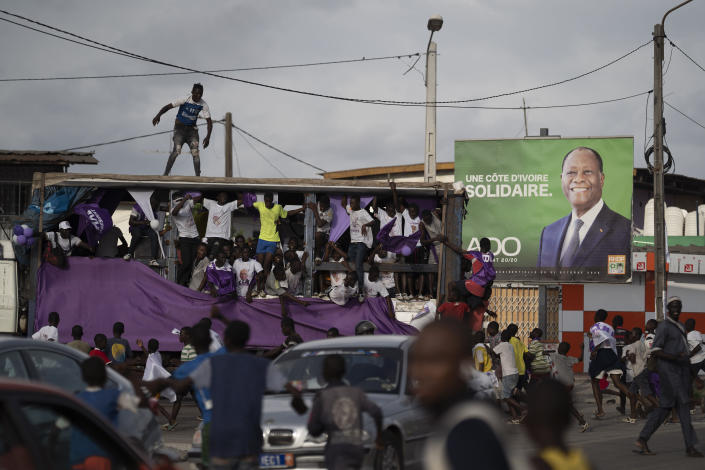 Supporters of the presidential candidate Kouadio Konan Bertin, ride a sound truck as they pass by an outdoor with a picture of the Ivory Coast President Alassane Ouattara during a final campaign rally in Abidjan, Ivory Coast, Thursday, Oct. 29, 2020. Bertin, known as KKB, has presented his candidacy as an independent candidate for the upcoming Oct. 31 election, and said he would not join the boycott proposed by two main opponents of Ivory Coast President Alassane Ouattara. (AP Photo/Leo Correa)