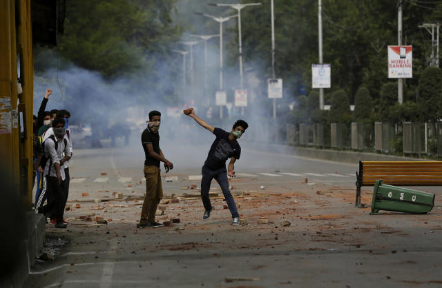 <p>Kashmiri students throw stones on Indian policemen as they clash in Srinagar, Indian controlled Kashmir, May 9, 2017. The students have been protesting since last month against a police raid in a college in southern Pulwama town in which at least 50 students were injured. (Photo: Mukhtar Khan/AP) </p>