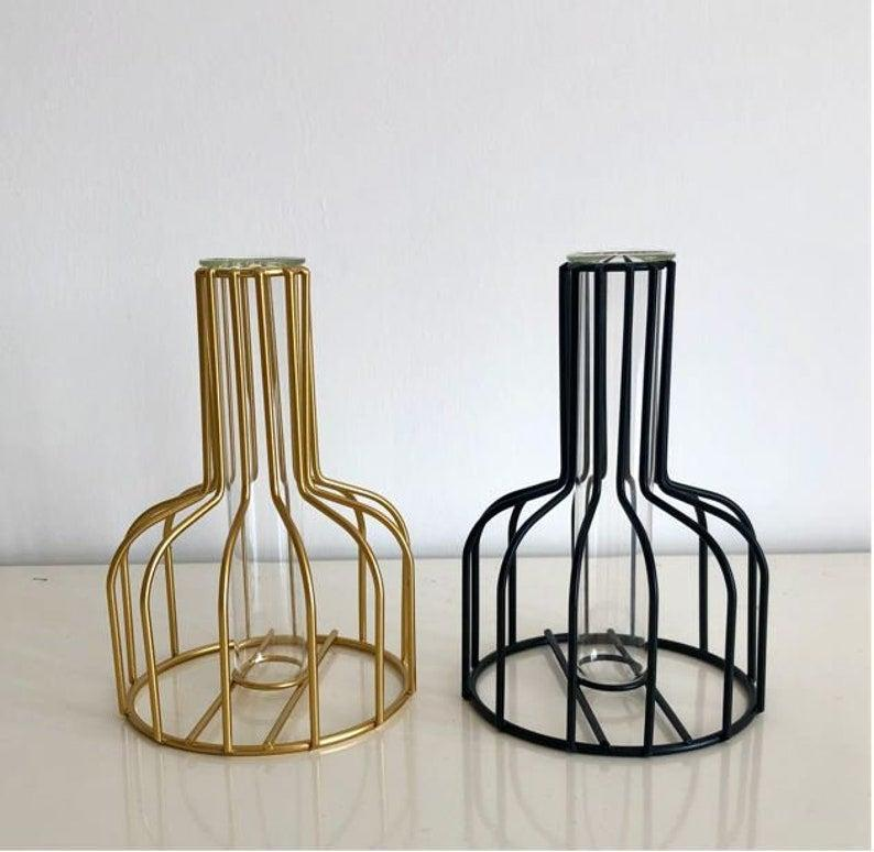 """Another black iron frame, this vase works for fresh or dried flowers, thanks to its cleverly concealed glass tube.<br><br><strong>PinkToucanCo</strong> Modern Nordic Iron Vase, Black or Gold, $, available at <a href=""""https://www.etsy.com/uk/listing/1039703120/modern-nordic-iron-vase-o-ideal-for"""" rel=""""nofollow noopener"""" target=""""_blank"""" data-ylk=""""slk:Etsy"""" class=""""link rapid-noclick-resp"""">Etsy</a>"""