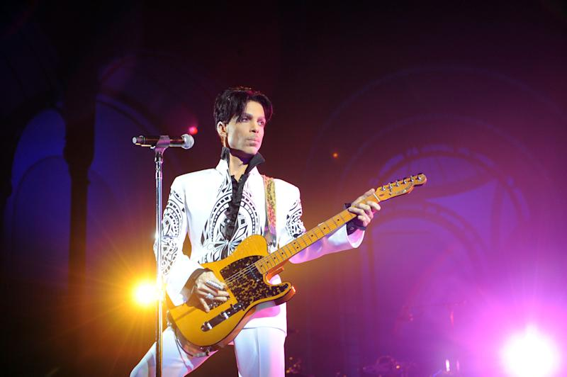 Prince on stage with his guitar and he looks dazzling in white and black print shirt and pant to match.