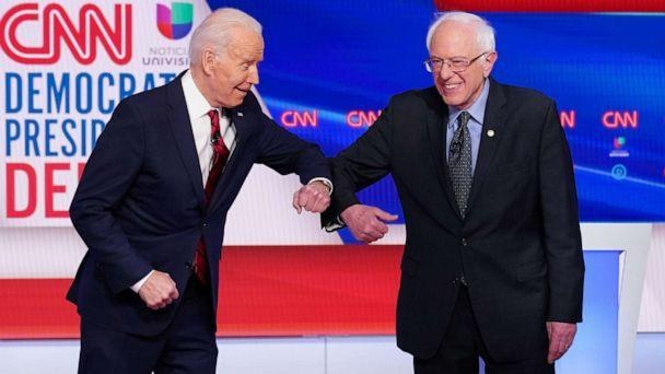 PHOTO: Democratic presidential hopefuls former Vice President Joe Biden and Sen. Bernie Sanders greet each other with an elbow bump as they arrive for the a presidential debate at a CNN Washington Bureau studio, March 15, 2020. (Mandel Ngan/AFP via Getty Images, FILE)