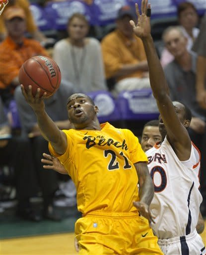 Long Beach State guard Larry Anderson (21) shoots a layup while being defended by Auburn center Willy Kouassi, right, in the first half of an NCAA college basketball game Friday, Dec. 23, 2011, in Honolulu. (AP Photo/Eugene Tanner)