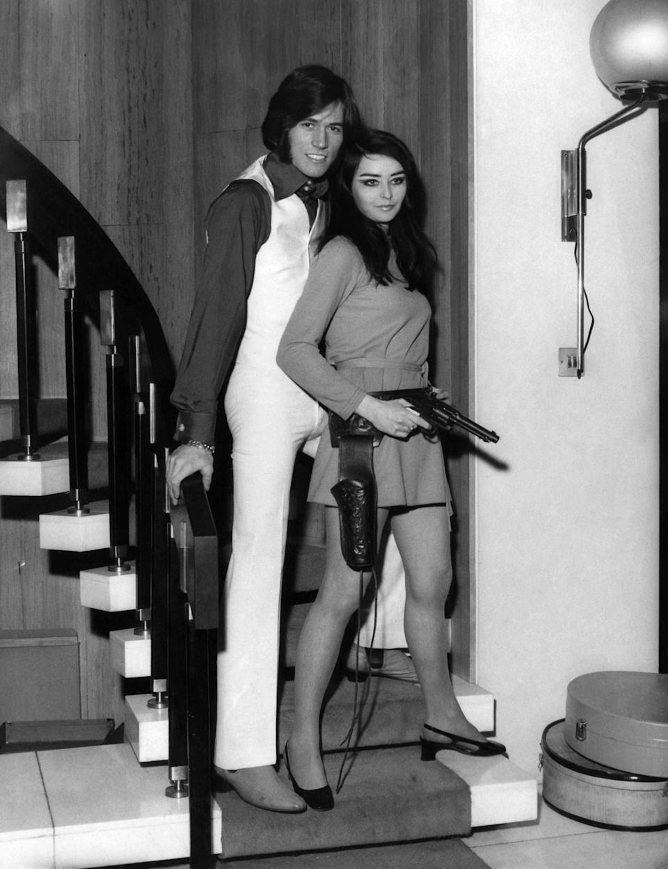 Barry Gibb pictured at home with his girlfriend Linda Gray, posing with a model Colt 0.45 on the staircase at his home. December 1968. (Photo by Daily Mirror/Mirrorpix/Mirrorpix via Getty Images)