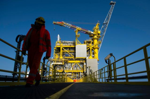 An employee walks along an oil platform on the North Sea, about 45 miles east of the Aberdeen. (Andy Buchanan/AFP via Getty Images)