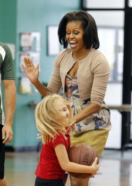 First Lady Michelle Obama has fun with a young girl at Holiday Park Gym, Wednesday, Aug. 22, 2012 in Fort Lauderdale, Fla. (AP Photo/Alan Diaz)