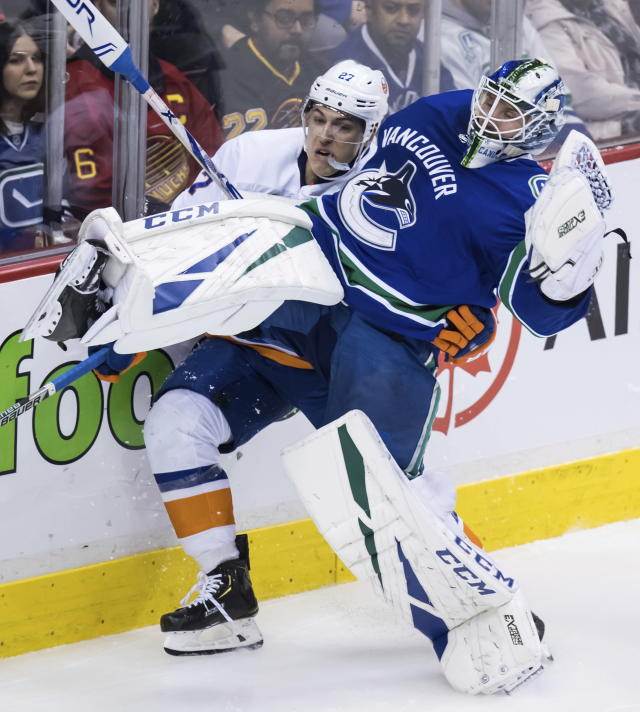 Vancouver Canucks goalie Jacob Markstrom, front, of Sweden, loses his balance as New York Islanders' Anders Lee skates into him during the second period of an NHL hockey game Saturday, Feb. 23, 2019, in Vancouver, British Columbia. (Darryl Dyck/The Canadian Press via AP)