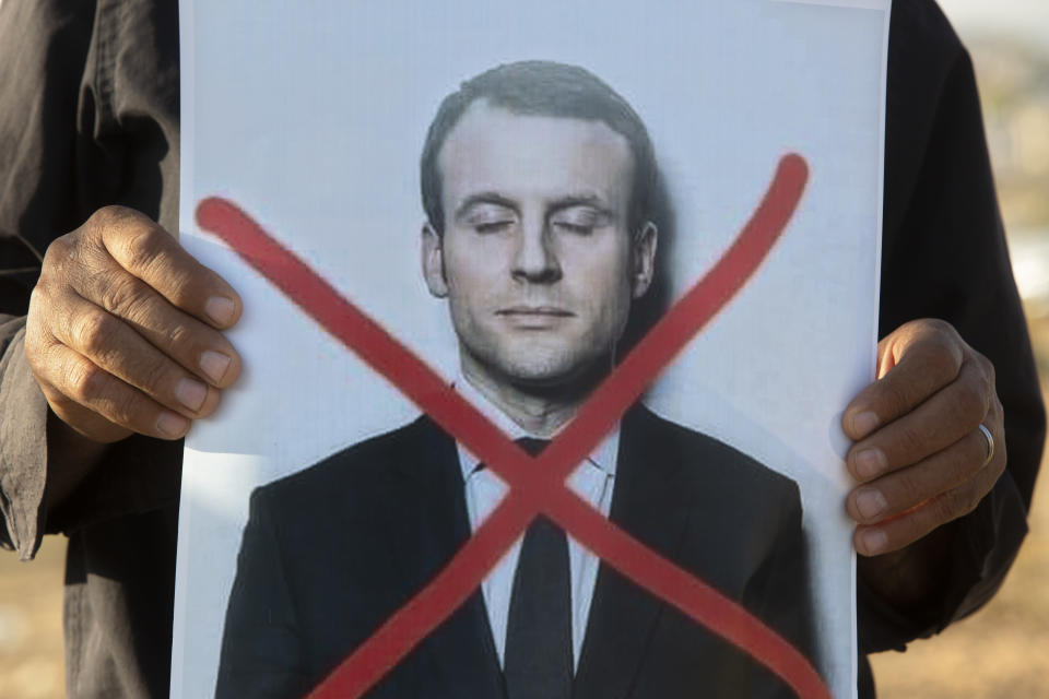 An Israeli Arab protester holds a defaced picture of French President Emmanuel Macron, during a small demonstration protesting published caricatures of the Prophet Muhammad deemed insulting and blasphemous, in Hura, a Bedouin village in the Negev desert, Israel, Monday, Oct. 26, 2020. (AP Photo/Sebastian Scheiner)
