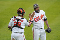 Baltimore Orioles catcher Pedro Severino (28) and relief pitcher Cesar Valdez celebrate after defeating the New York Yankees 10-6 during a baseball game, Sunday, May 16, 2021, in Baltimore. (AP Photo/Julio Cortez)