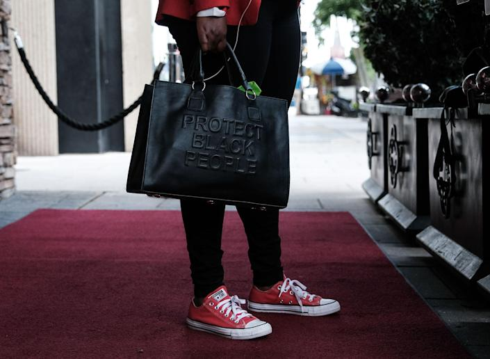 """Texas Representative Jasmine Crockett holds a handbag with the words """"Protect Black People"""" in Washington, D.C., on July 16.<span class=""""copyright"""">Michael A. McCoy for TIME</span>"""
