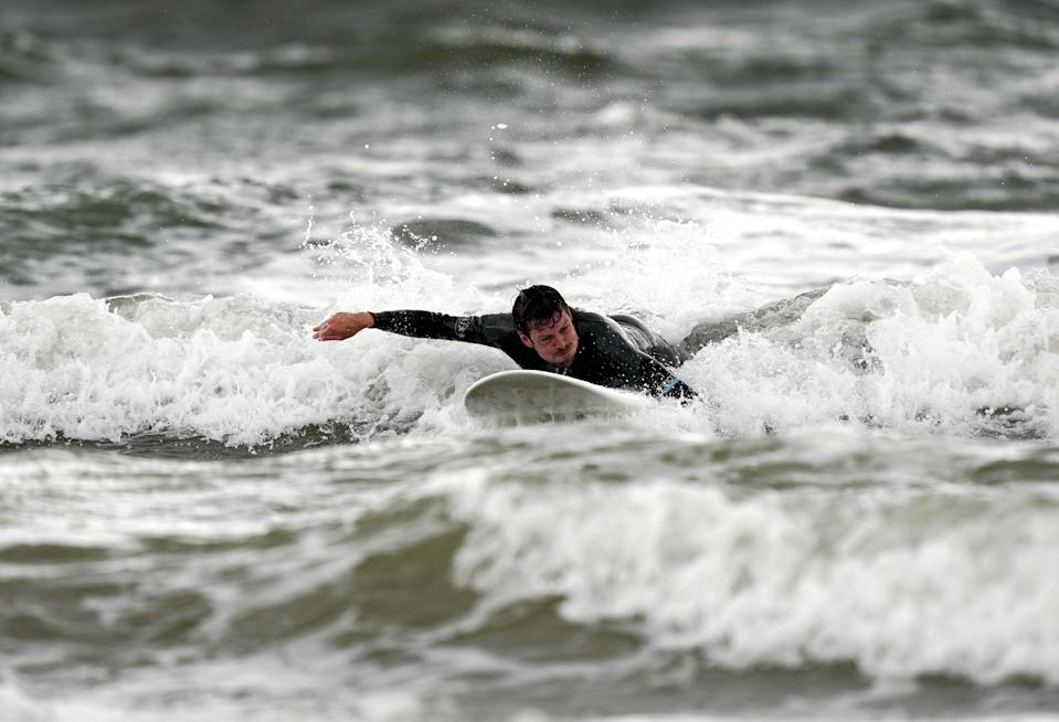 A surfer enjoys the waves in Porthcawl, Wales (PA Wire)