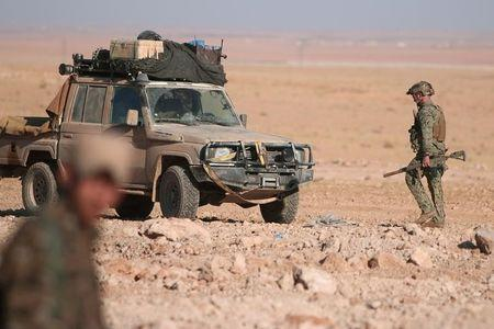 A U.S. fighter walks with his weapon near a military vehicle, north of Raqqa city
