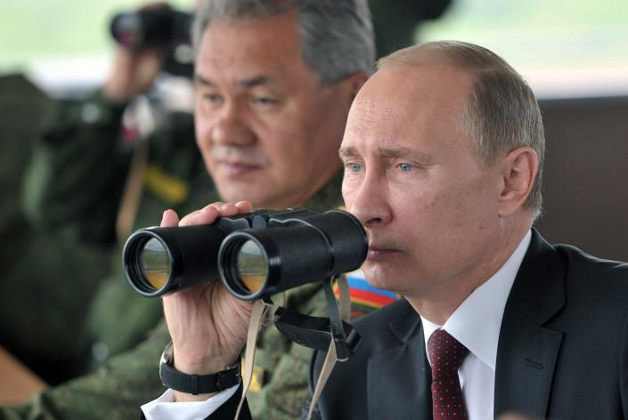 FILE - In this Tuesday, July 16, 2013 file photo Russian President Vladimir Putin, flanked by Defense Minister Sergei Shoigu, uses binocular as he watches military exercise near Yuzhno-Sakhalinsk, on Sakhalin Island, Russia. President Vladimir Putin on Wednesday, Feb. 26, 2014, ordered massive exercises involving most of its military units in western Russia amid tensions in Ukraine. (AP Photo/RIA Novosti, Alexei Nikolsky, Presidential Press Service, Pool)
