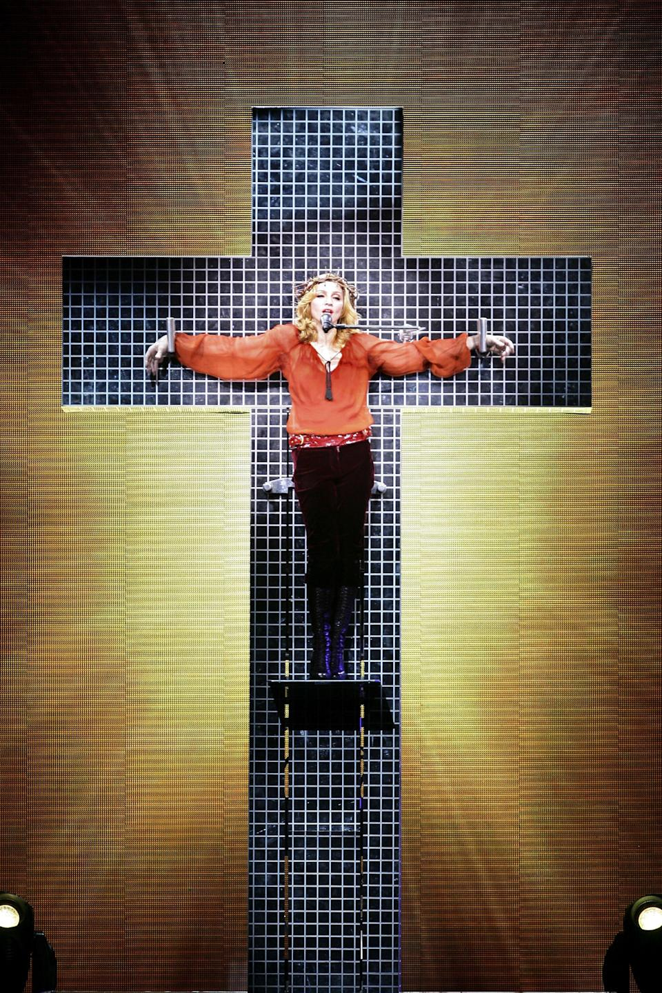 """<p>She's still into the Catholic stuff, though! In her most literal tribute to Jesus Christ yet, she belted the 1986 ballad """"<a href=""""https://www.youtube.com/watch?v=2JvK3U2gpsQ"""" rel=""""nofollow noopener"""" target=""""_blank"""" data-ylk=""""slk:Live to Tell"""" class=""""link rapid-noclick-resp"""">Live to Tell</a> """" while mock-crucified to a disco-fied cross for her 2006 Confessions Tour — once again angering the Catholic Church, as well as the Church of England. """"I don't think Jesus would be mad at me and the message I'm trying to send,"""" <a href=""""https://www.npr.org/templates/story/story.php?storyId=5658956"""" rel=""""nofollow noopener"""" target=""""_blank"""" data-ylk=""""slk:Madonna told the Daily News"""" class=""""link rapid-noclick-resp"""">Madonna told the <em>Daily News</em></a> of the incident.</p><span class=""""copyright"""">Photo: Dave Hogan/Getty Images.</span>"""