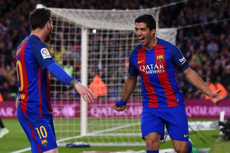 Barcelona's forward Luis Suarez (R) celebrates his goal with forward Lionel Messi during the Spanish league football match FC Barcelona vs Sevilla FC at the Camp Nou stadium in Barcelona on April 5, 2017