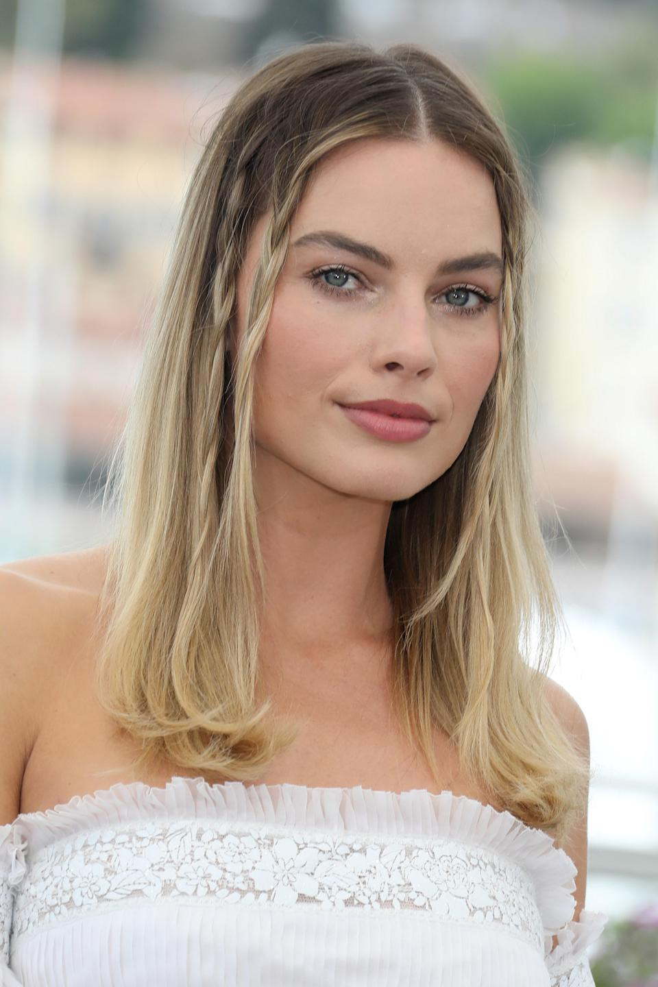 """Multiple braids like Margot Robbie's, here, have a more '70s feel, or you can go for just one on each side for '90s vibes. Moroccanoil celebrity stylist <a href=""""https://www.thewallgroup.com/artist/bryce-scarlett"""" rel=""""nofollow noopener"""" target=""""_blank"""" data-ylk=""""slk:Bryce Scarlett"""" class=""""link rapid-noclick-resp"""">Bryce Scarlett</a>, who did this Sharon Tate–inspired look on Robbie, says the key to keeping it current is by not being too precious with the style. To get a similar look at home, skip the hair ties, and saturate the end of your braids with hairspray (he likes <a href=""""https://shop-links.co/1709290983046944131"""" rel=""""nofollow noopener"""" target=""""_blank"""" data-ylk=""""slk:Moroccanoil Luminous Hairspray Strong"""" class=""""link rapid-noclick-resp"""">Moroccanoil Luminous Hairspray Strong</a>). Clip the ends while the hairspray is drying (<a href=""""https://shop-links.co/1710323835641021551"""" rel=""""nofollow noopener"""" target=""""_blank"""" data-ylk=""""slk:setting clips like these work best"""" class=""""link rapid-noclick-resp"""">setting clips like these work best</a>), and then remove them right before you head out the door."""