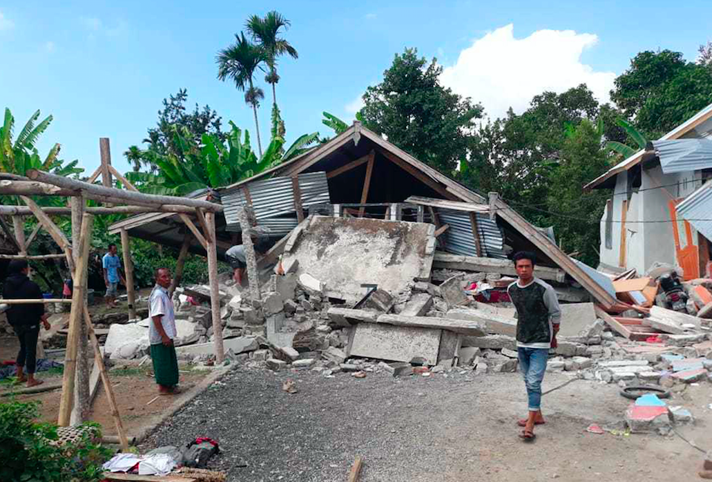 <em>Villagers walk near destroyed homes in an area affected by the early morning earthquake at Sajang village, Sembalun (AP)</em>