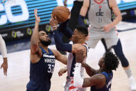 Washington Wizards guard Russell Westbrook, center, goes to the basket against Minnesota Timberwolves center Karl-Anthony Towns (32) and forward Anthony Edwards (1) during the first half of an NBA basketball game, Saturday, Feb. 27, 2021, in Washington. (AP Photo/Nick Wass)