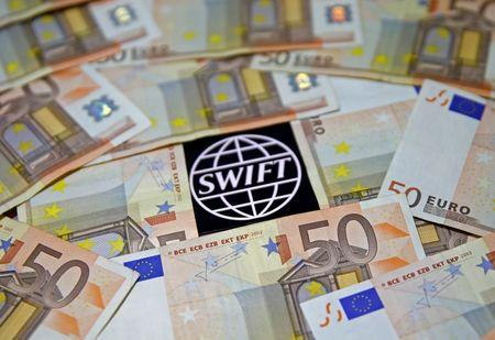 FILE PHOTO: Swift code bank logo is displayed on an iPhone 6s among Euro banknotes in this picture illustration