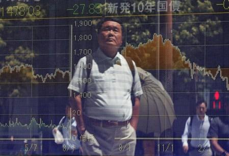 Passersby are reflected on a screen displaying graphs of market indices outside a brokerage in Tokyo