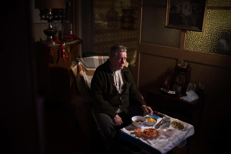 """Álvaro Puig Moreno watches television while eating a his Christmas Eve dinner at his home in Barcelona, Spain, Thursday, Dec. 24, 2020. """"The solitude gets to me these days, I often feel depressed,"""" Puig said. """"These holidays, instead of making me happy, make me sad. I hate them. Most of family has died, I am one of the last ones left. I will spend Christmas at home alone because I don't have anyone to spend them with.""""(AP Photo/Emilio Morenatti)"""