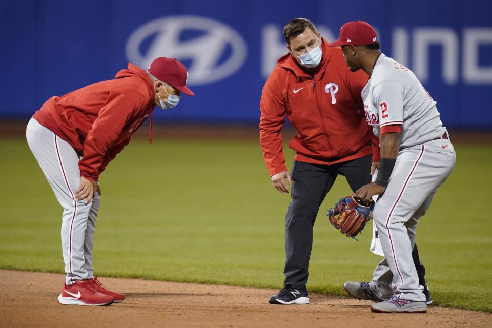 Philadelphia Phillies manager Joe Girardi, left, watches as a trainer checks on shortstop Jean Segura, right, during the sixth inning of a baseball game against the New York Mets Wednesday, April 14, 2021, in New York. (AP Photo/Frank Franklin II)