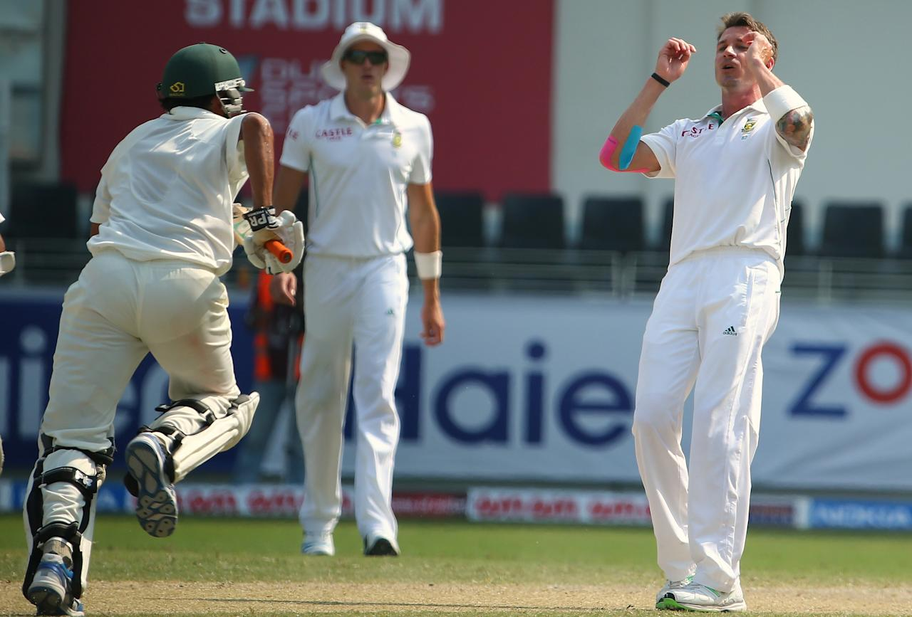 South African bowler, Dale Steyn (R), of South Africa gestures as Younis Khan of Pakistan runs between wickets during the third day of the second Test cricket match between Pakistan and South Africa in Dubai on October 25, 2013.      AFP PHOTO/ MARWAN NAAMANI        (Photo credit should read MARWAN NAAMANI/AFP/Getty Images)