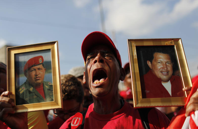A supporter of Venezuela's late President Hugo Chavez holds images of him while his coffin passes in the street from the hospital where he died on Tuesday to a military academy where his body will lie in state until his funeral in Caracas, Venezuela, Wednesday, March 6, 2013. Seven days of mourning were declared, all schools were suspended for the week and friendly heads of state were expected for an elaborate funeral Friday. (AP Photo/Rodrigo Abd)