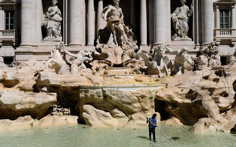 A worker collecting coins in the Trevi Fountain in Rome, as part of a regular monthly cleaning routine.  - AFP