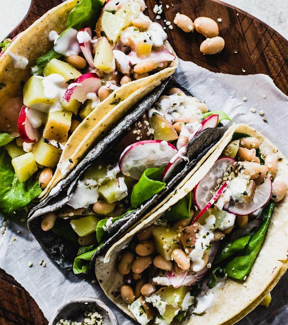 """<p>Black and refried beans usually get the spotlight in the tacoverse, but white beans, with their light and buttery taste, are a perfect medium to top with flavorful spices and sauces.</p> <p>Get the recipe <a href=""""https://heartbeetkitchen.com/2018/recipes/vegetarian-spring-tacos-with-white-beans/"""" rel=""""nofollow noopener"""" target=""""_blank"""" data-ylk=""""slk:here"""" class=""""link rapid-noclick-resp"""">here</a>.</p>"""
