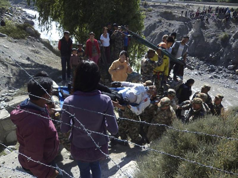 Nepalese rescuers carry on a stretcher, the injured pilot of the state-owned Nepal Airlines plane that crashed on the banks of Kaligandaki river at Jomsom, some 200 kilometers (125 miles) northwest of Katmandu, Nepal, Thursday, May 16, 2013. The plane crashed while trying to land at a mountain airstrip in northern Nepal early Thursday, injuring all 21 people on board. No one was killed. (AP Photo/Ananda Subedi)
